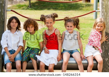 Group of kids sitting together in park. - stock photo