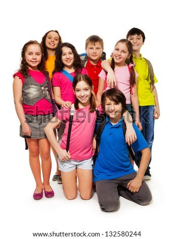 Group of 8 kids standing together with backpacks, smiling, laughing, on white - stock photo