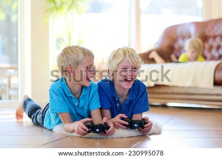 Group of kids twin teenage brothers having fun after school day playing video game holding joysticks in hands lying cozy on tiles floor on warm lambskin in bright sunny living room with big windows  - stock photo