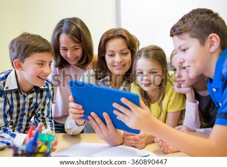 group of kids with teacher and tablet pc at school