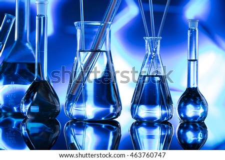 Group of laboratory flasks empty or filled with a clear liquid on blue tint scientific graphics background and their reflection on a table