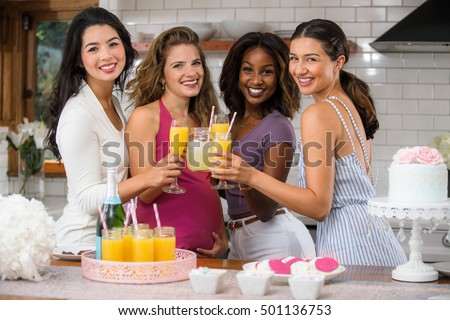 Group of ladies friends cheers toast wine mimosas at a baby shower get together