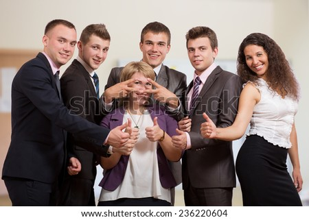 Group of laughing business people. Six business people make funny gestures. The stay inside of office interior and dressed according to business dress code. - stock photo