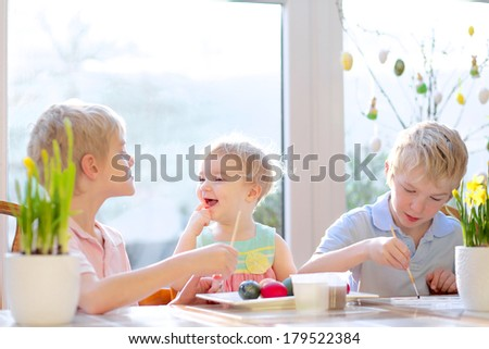 Group of laughing kids from one family, two twin brothers and their little toddler sister, decorating and painting Easter eggs sitting together in the kitchen on a sunny day. - stock photo