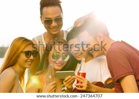 Group of laughing young people watching funny video or photo on the smartphone