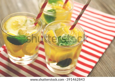 Group of lemonades with lemon and mint on striped cloth, closeup