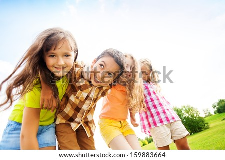 Group of little 6 and 7 years old smiling kids smiling standing outside in the park - stock photo