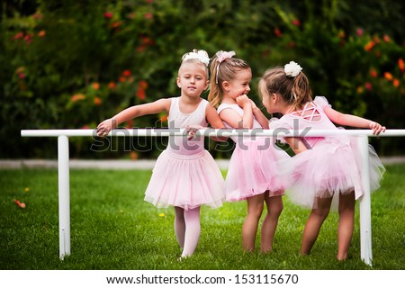 Group of little girls doing ballet bar exercises at beautiful summer garden background - stock photo