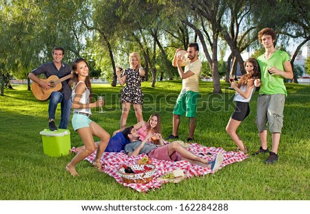 Group of lively happy teenage young friends enjoying a picnic outdoors dancing and singing along to guitar music played by one of the boys - stock photo