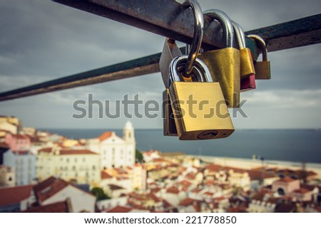 Group of love padlocks attached to a fence over beautiful Lisbon view - stock photo