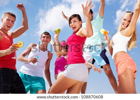 Group of lovely young people dancing and jumping outdoor - stock photo