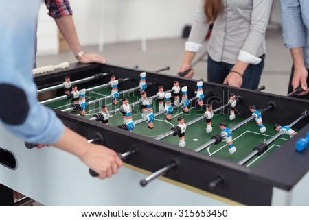 Group of Male and Female Office Workers Playing Table Soccer Game During their Break Time to Relieve Work Stress. - stock photo