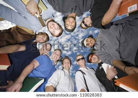Group of male friends forming huddle against sky