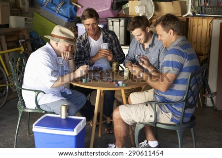 Group Of Male Friends Playing Cards In Garage - stock photo