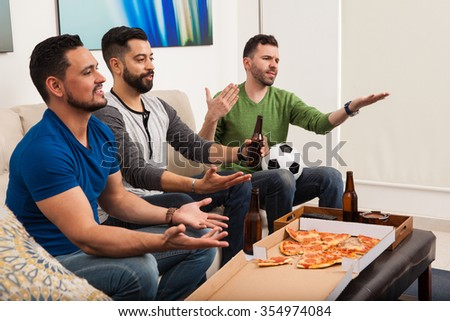Group of male friends yelling at the referee while they watch a soccer game on TV - stock photo