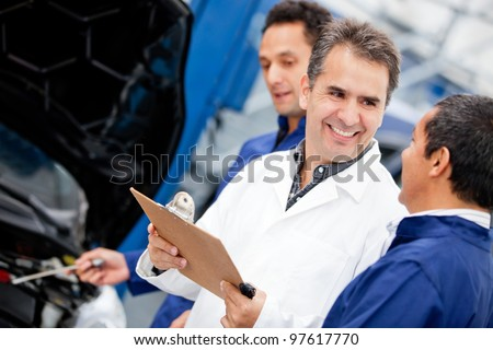Group of male mechanics working at a car garage - stock photo