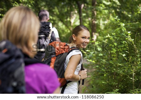 group of man and women during hiking excursion in woods, with woman looking at camera over shoulders and smiling. Waist up - stock photo