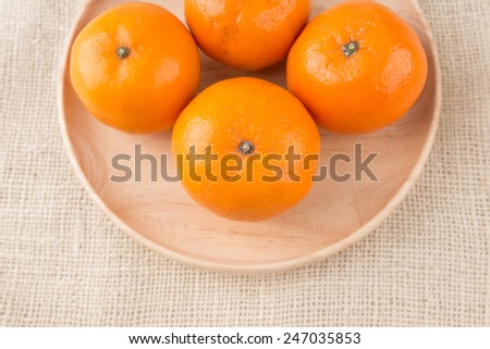 Group of mandarin oranges, tangerines fruit on wooden dish