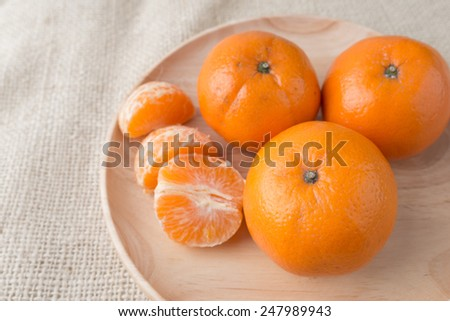 Group of mandarin oranges, tangerines fruit put in wood plate on burlap sack background