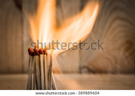 group of match is ignite on a blurry wood background. Selective focus. - stock photo