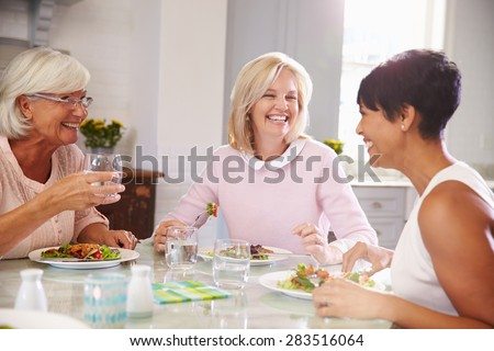 Group Of Mature Female Friends Enjoying Meal At Home - stock photo