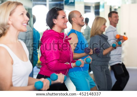 Group of mature men and women training in  gym with dumbbells. Selective focus