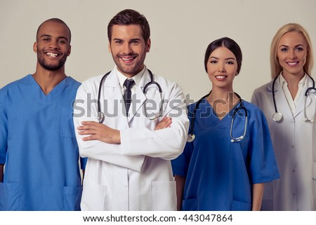 Group of medical doctors of different nationalities and genders is looking at camera and smiling, standing on gray background