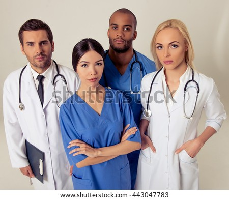 Group of medical doctors of different nationalities and genders is looking at camera, standing on gray background