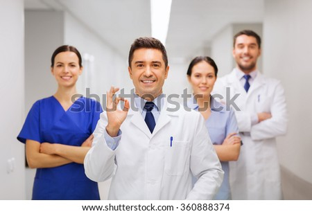 group of medics at hospital showing ok hand sign - stock photo