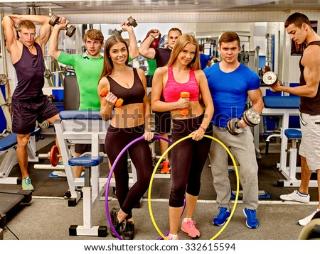 Group of men and happy women trained in the gym using the equipment, dumbbells and fitnes hoop. Group portrait. - stock photo