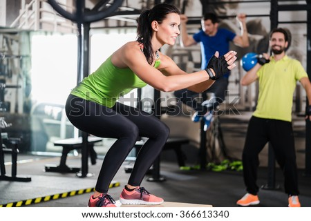 Group of men and woman in functional training gym doing fitness exercise - stock photo