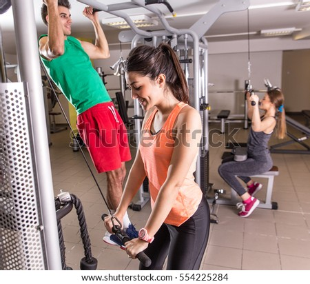 Group of men and woman in training gym doing fitness exercise.