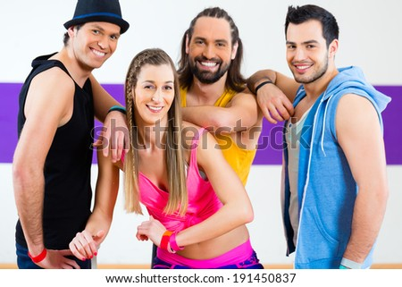 Group of men and women dancing zumba fitness choreography in dance school