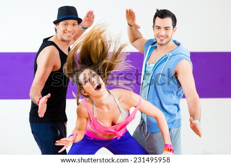 Group of men and women dancing zumba fitness choreography in dance school - stock photo