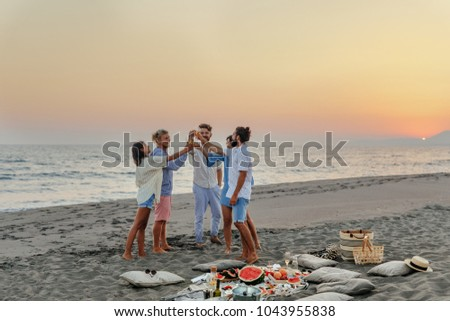 Group of men and women having fun toasting with champagne on beach party.