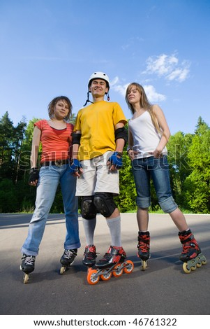 Group of men and women on rollerblades having fun at park - stock photo