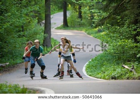 Group of men and women on rollerblades skating at park