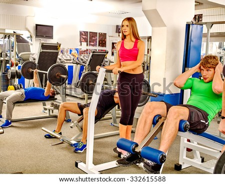 Group of men and women trained in the gym using the equipment and barbells. The overall plan . - stock photo