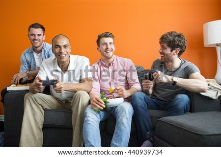 Group of men are having fun at home, playing video games.