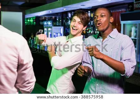 Group of men dancing near bar counter in bar - stock photo