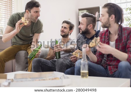 Group of men eating pizza and drinking a beer