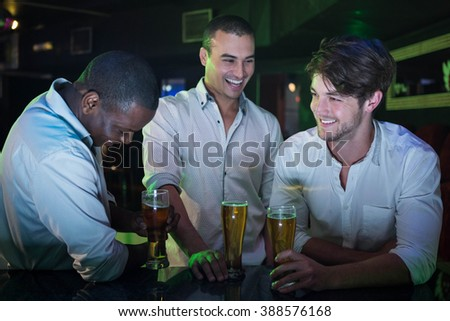 Group of men partying with glass of beer at bar counter in bar - stock photo