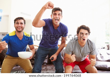 Group Of Men Sitting On Sofa Watching Sport Together - stock photo
