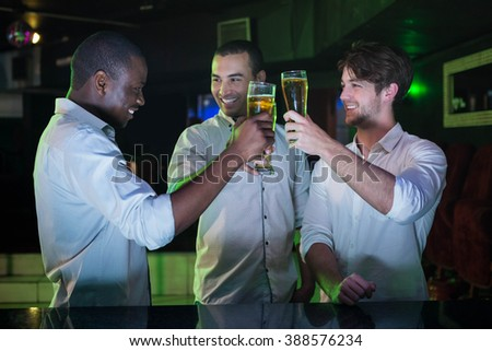 Group of men toasting with glass of beer in bar - stock photo