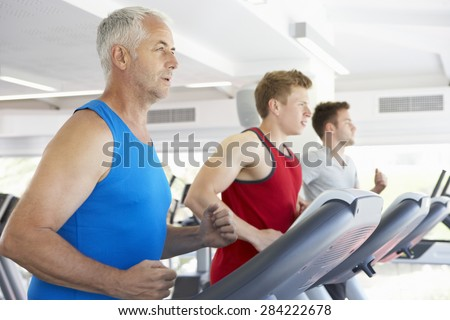 Group Of Men Using Running Machines In Gym