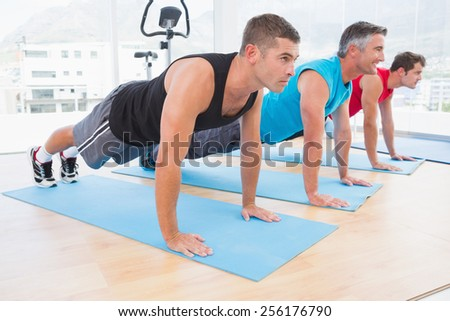 Group of men working on exercise mat in fitness studio - stock photo