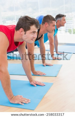 Group of men working on exercise mat in fitness studio