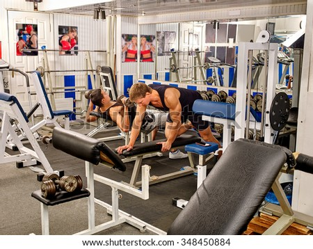 Group of men working on simulator his body at gym with mirror and picture on wall. - stock photo