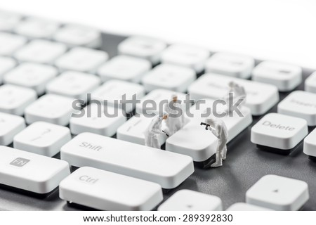 Group of miniature criminalists inspecting computer keyboard.  Cybercrime concept. Macro photo - stock photo