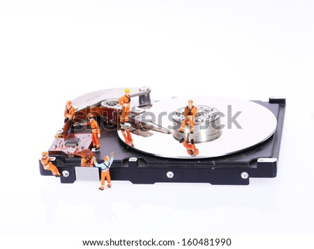 Group of miniature technicians repair hard drive - stock photo